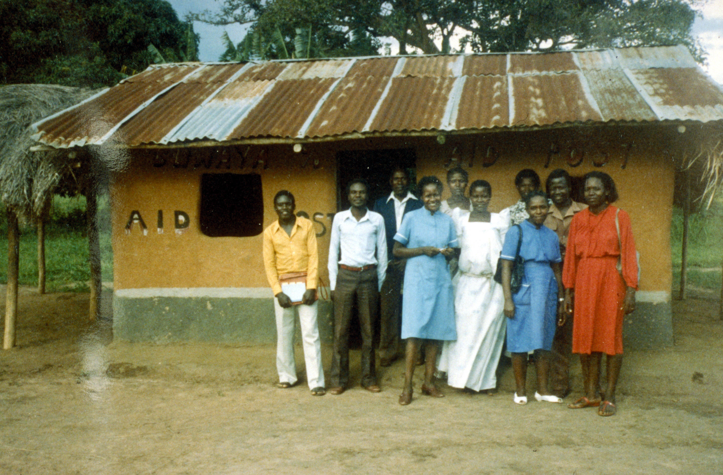 A group of smiling African men and women outside a hut with 'AID' painted on the wall