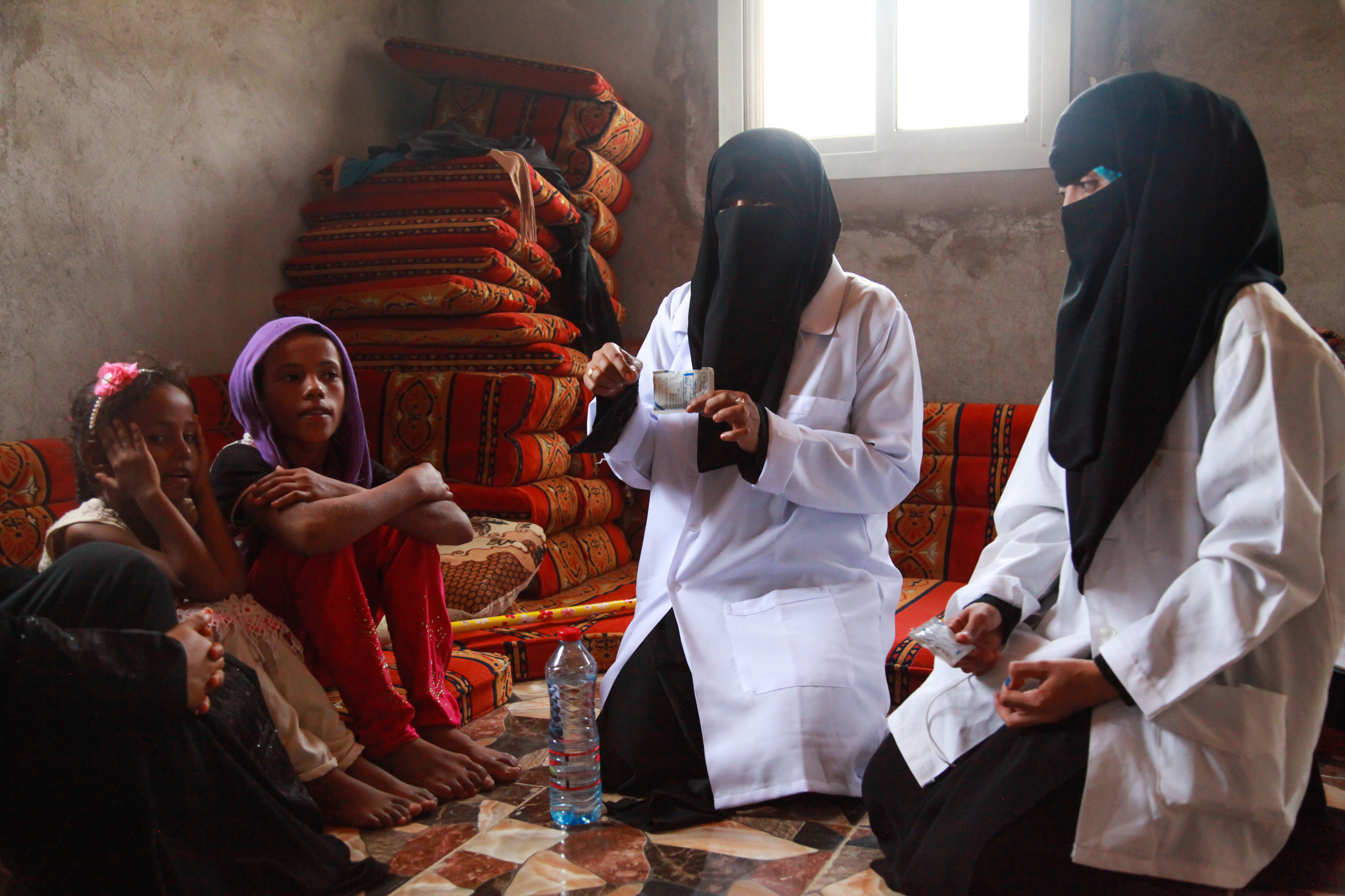 Photograph of two female medics in white coats and black hijabs tending two African women who are sitting on the floor in their home