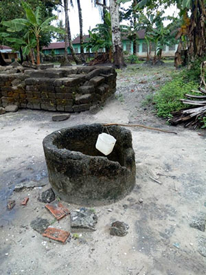 A well with broken walls and a plastic bucket in a semi-rural setting