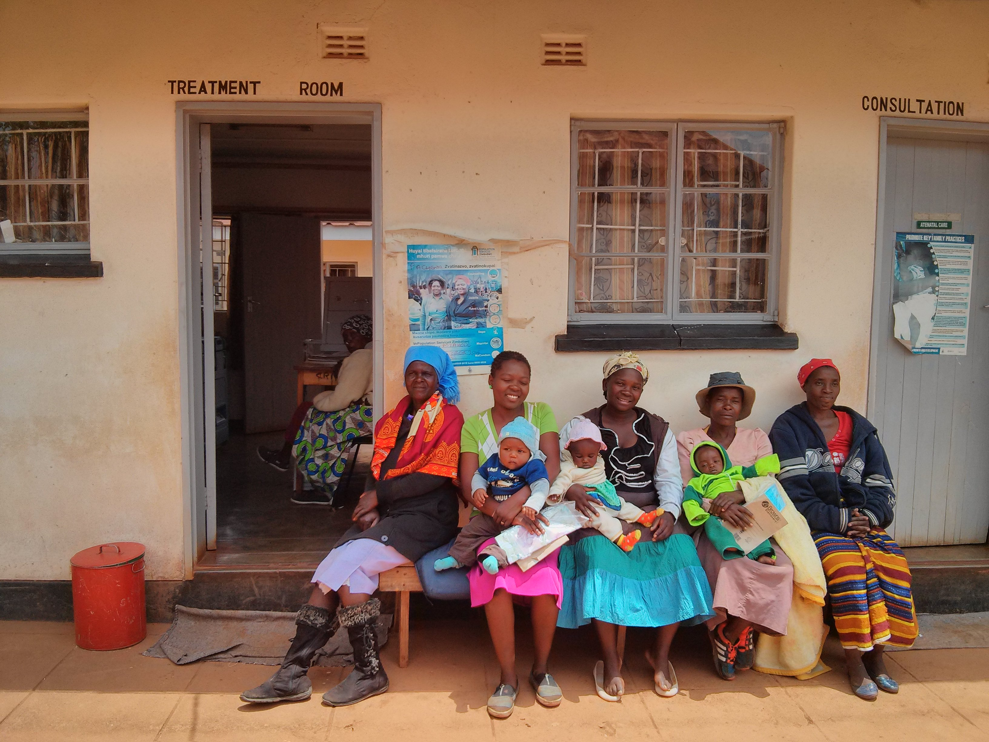 A row of seated African women and babies sitting outside a health centre