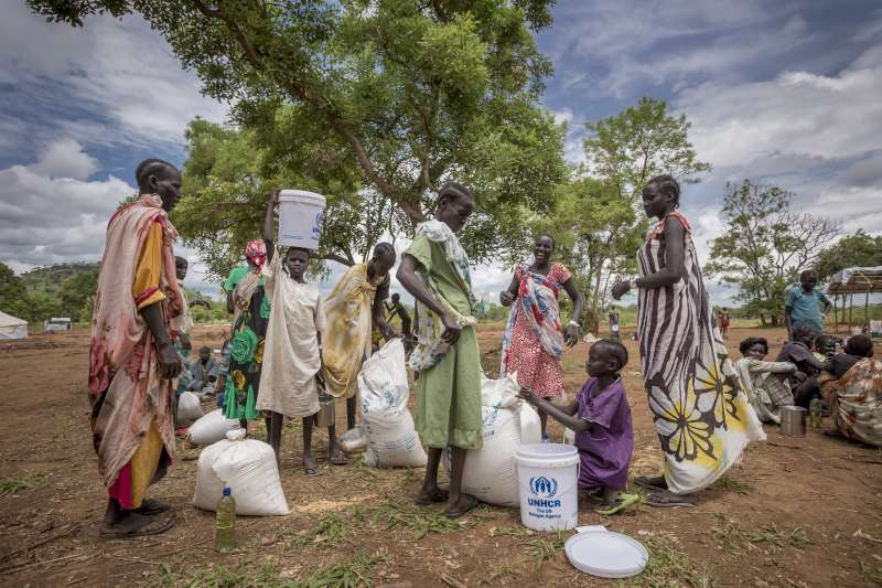 African women and children with bags and buckets marked 'UNHCR'