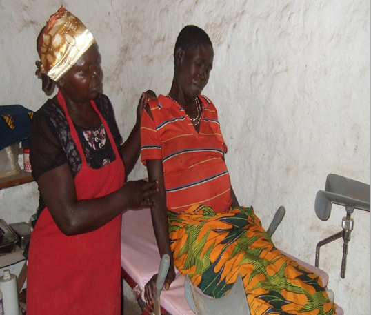 An African woman in an apron tends to a pregnant African woman who is sitting on a bed looking uncomfortable