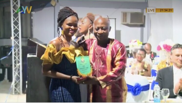 A smiling woman receives an award from a a smiling man